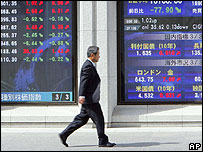 Man walks past electric stock indicators in Tokyo