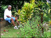 Manasa Lalaqila sitting by his son's grave in his garden