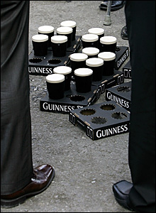 Race goers surround pints of Guinness