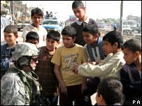 Children gather around a US soldier in Sadr City