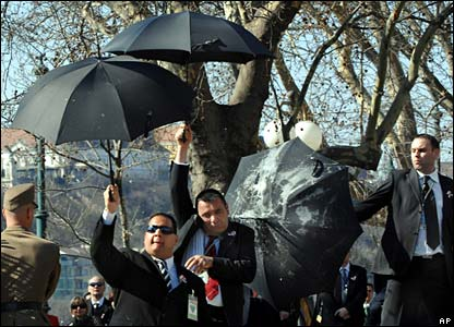 Security guards protect senior politicians from missiles with umbrellas