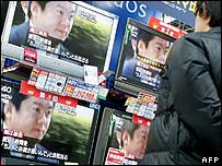 A man watches television news reports on Mr Horie's court verdict