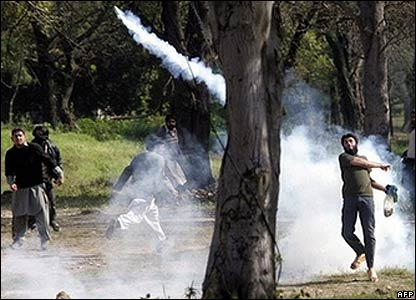 Protester throws a tear gas shell in Islamabad