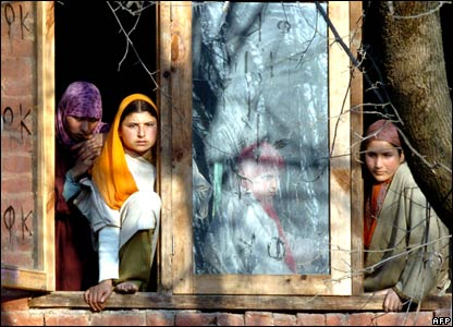 Kashmiri women watch a funeral from a window in Indian-administered Kashmir