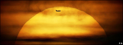 An aircraft flies in front of the sun