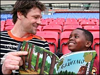 Wigan defender Arjan de Zeeuw reads to a local school boy
