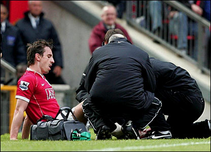 Gary Neville receives treatment on the pitch