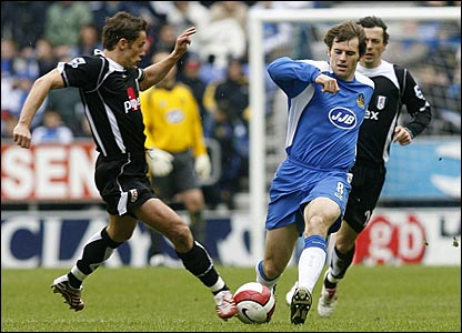 Fulham's Michael Brown and Wigan Athletic's Kevin Kilbane tussle for the ball