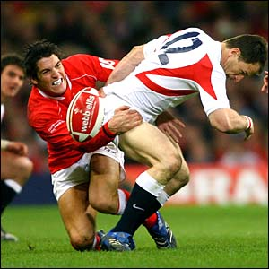 England's Mike Catt is tackled by Wales' James Hook