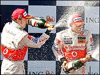 Fernando Alonso and Lewis Hamilton celebrate on the podium after the Australian Grand Prix