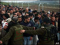 Israeli soldiers hold back Palestinians at Hawara checkpoint, Nablus