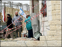 Jewish settlers stand at the entrance to a building they occupied