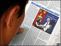 Man reading newspaper about Angelina Jolie in Vietnam
