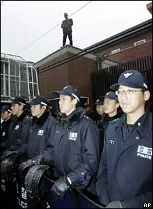 South Korean police officers guard the Japanese embassy compound in Seoul, South Korea, as protester Oh Sung-taek stands atop its walls
