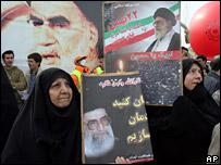 Iranian women hold portraits of Ayatollah Ali Khamenei