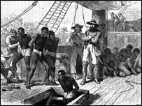 Slave traders with slaves manacled, chained, in leg irons