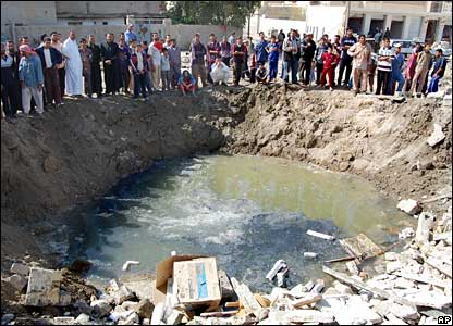 People gather around a a bomb crater in Ramadi, Iraq