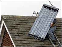 A man putting a solar panel on a roof