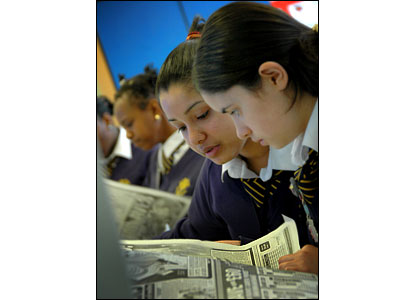 Students research news stories in the daily papers
