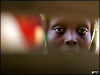 Una mujer desplazada mira a través de las tablas del barracón donde vive, en un campamento de refugiados de la ciudad de Nyala en Darfur