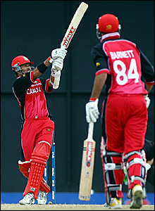 Canada's John Davison (left) launches another ball to the boundary