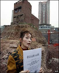 House owner Wu Ping with the court verdict beside her home in Chongqing on 22 March 2007