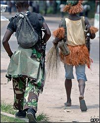 Soldiers loyal to former Vice President Jean-Pierre Bemba wearing tribal dress walk down a street in Kinshasa