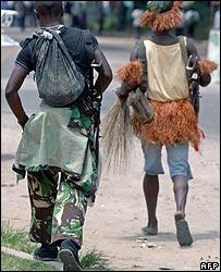 Soldiers loyal to former Vice President Jean-Pierre Bemba wearing tribal dress walk down a street in Kinshasa