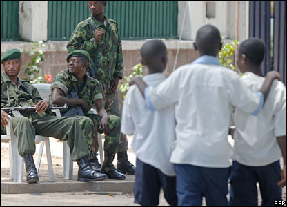 Schoolchildren pass by troops loyal to Mr Bemba