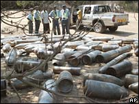 Police inspect artillery shells after the depot blasts in Maputo