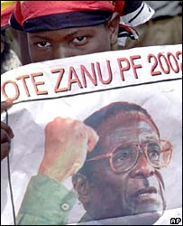 A Zanu-PF supporter holds an election poster during the 2002 campaign