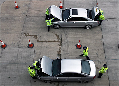 Police officers carry out security checks on cars arriving at Wembley