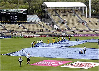 Ground staff deal with the rain-soaked ground in St Lucia