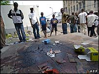 A group of people stand around a pool of blood in Kinshasa