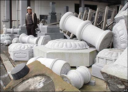 A man inspects the damage at a stone carving centre