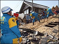 Japanese policemen clear rubble from a collapsed house in Wajima on 26 March 2007