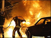 Firefighters extinguish a fire in a burning car during the rioting