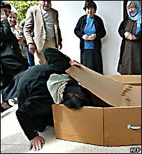 عراقية تفتح تابوتا لتقبل قبلة الوداع جثمان القتيل خلال الجنازة في كركو، 27 مارس/آذار 2007