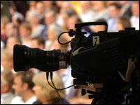 A television camera (foreground) and a studio audience (background)