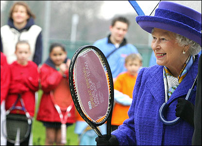 The Queen is presented with a tennis racket signed by all the members of the British Davis Cup team