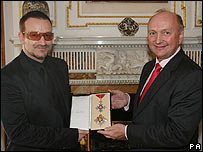 Bono receiving his honorary knighthood from British Ambassador David Reddaway