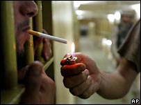 Abu Ghraib guard lights cigarette of a prisoner