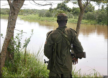 A Ugandan soldier stands by a river