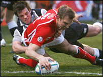 Scarlets wing Dafydd James forces his way over for the opening try