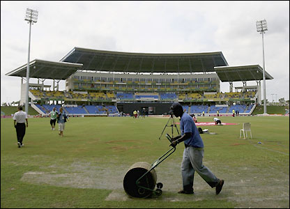 A member of the groundstaff tries to clear water from the outfield