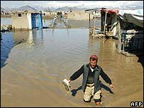 An Afghan man wades through floodwaters in Kabul