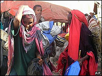 Somali women carry belongings as they leave Mogadishu