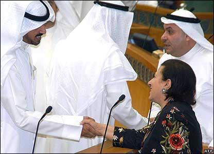 Kuwait's new Education Minister Nuriya al-Sebih shakes hands with an MP.