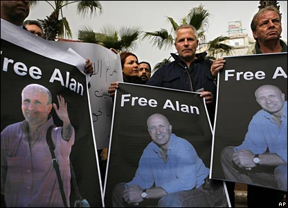 Foreign and Palestinian journalists hold portraits of Alan Johnston at a demonstration in the West Bank town of Ramallah