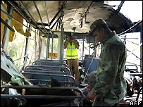 A Sri Lankan soldier inspects the inside of the bombed bus